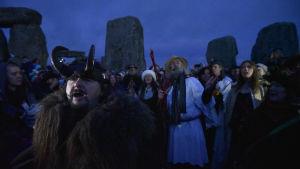 Människor firar vintersolståndet vid Stonehenge. I förgrunden en man med en behornad hjälm på huvudet.