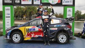 Sebastien Ogier (t.h.) med sin Ford Fiesta på ett podium.