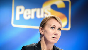 Hanna Mäntylä med Sannfinländarnas logo i bakgrunden.