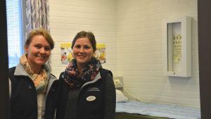 Skolhälsovårdarna Nina Herrgård och Marion Salmela står i sitt mottagningsrum på Korsholms högstadium. De har blåa jackor på sig och skarfar runt halsen.