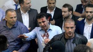 Flera män, en del av dem blodiga, samlade på ett ställe. I mitten står socialdemokratiske ledare i Makedonien Zoran Zaev som blöder från pannan. Han skjorta är också blodig.