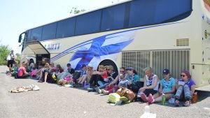 Människor (scouter) som sitter bredvid en buss och äter.
