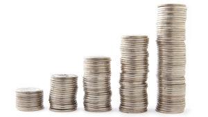 Mynt staplade i högar som blir högre och högre.