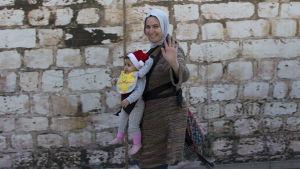 En muslimsk kvinna med sin baby i tomteluva i Betlehem på julafton.