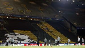 En öde stadion och spelare som värmer upp.