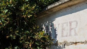 Graffiti med Enver Hoxhas namn i Porto Palermo i Albanien.