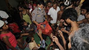 Indonesiska myndigheter delar ut mat åt rohingyaflyktingar som räddats till havs utanför den indonesiska kusten.