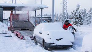 Bil som övergivits av asylsökande transporteras bort i Salla.