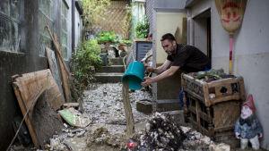 En man i Altstätten städar upp efter översvämningen.