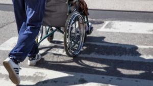 Dam i rullstol på övergångsställe
