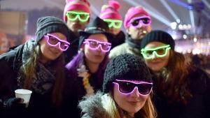 Sju personer med mössor och självlysande glasögon poserar för kameran på en nyårsfest i Berlin.