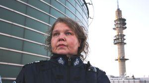 Kaarina Hazard seisoo rakennuksen vierellä, taustalla Pasilan tv-torni.