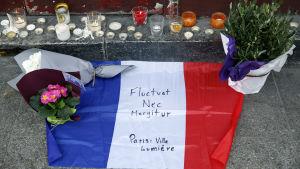 Blommor, ljus och den franska flaggan placerade på en gata i Paris.
