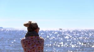 En kvinna tittar ut över havet.