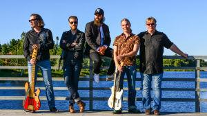 Wentus Blues Band. Medlemmmarna står på en brygga med hav i bakgrunden
