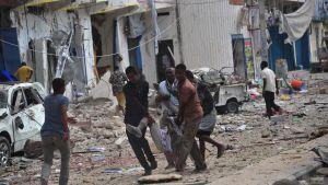 En skadad man bärs bort efter ett bombattentat mot ett hotell i Mogadishu 25.1.2017