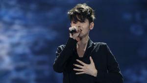 Man i mörka kläder sjunger i mikrofon