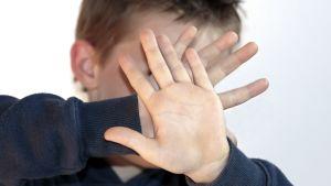 Ett barn håller upp händerna framför ansiktet.