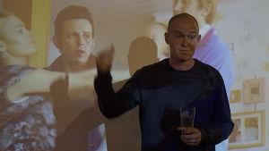 Ohjaaja Teppo Airaksinen osoittaa takanaan olevaa kuvaa.