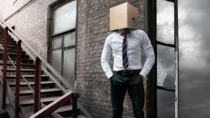 Man som gömmer ansiktet i en pafflåda.