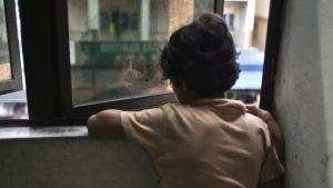Ett barn tittar ut genom ett fönster.