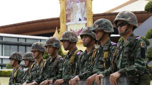 Thailändska soldater, i bakgrunden ett porträtt av kung Bhumibol