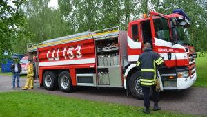 Brandbil parkerad på grusväg.