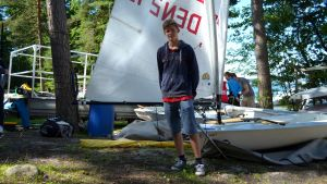 Pojke vid sin segelbåt