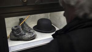 En besökare tittar på skoparet, plommonstopet samt promenadkäppen som tillhört Charlie Chaplins berömda luffar-karaktär.