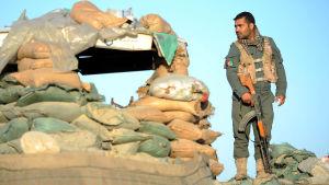 En soldat står vid sandsäckar vid en postering i Nangahaar kort efter ett dödligt angrepp i området.