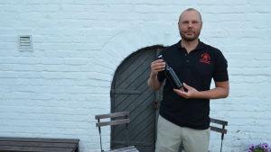 André Brunnsberg står framför sin källare där han förvarar sitt hembryggda öl.