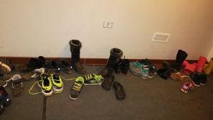 Koulun eteisessä on kenkiä sikin sokiin