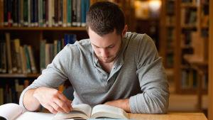 En ung man sitter vid ett bord och läser en bok.