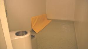 Fyllecell. Litet mörkt rum med gul madrass på golvet samt wc och lavoar.