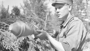 Alikersantti Frans Haapala kädessään panssarinyrkki.