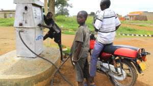 barn arbetar vid en handdriven bensinpump i norra uganda