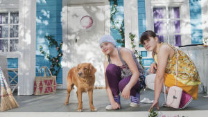 Glada och Ada och hunden Vakt på trappan till deras hus.