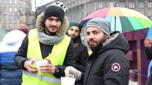 tre irakiska män med ett regnbågsparaply