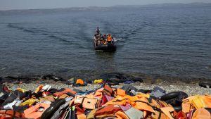 Gummibåt med asylsökande och migranter anländer till Lesbos, till en strand täckt av flytvästar 10.9.2015