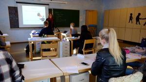 Lektion i samhällslära i ett klassrum i Rudolf Steinerskolan. Kameran fokuserar på en flicka med blond hästsvans.