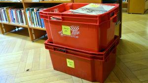 Damsugna böcker i lådor på väg tillbaka i hyllan på Lovisa huvudbibliotek