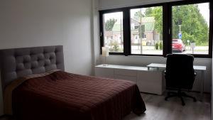 Ett sovrum med en säng, en byrå och ett skrivbord. Vid bordet står en skrivbordsstol.