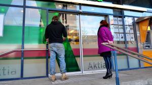 Bankkunder väntar på att bankkontoret öppnar.