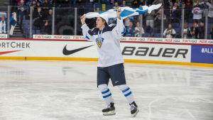Blåvit finländsk juniorishockeyspelare håller upp finska flaggan.