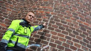 Mikael Sparf står iklädd neongula arbetskläder invid tegelväggen av den gamla skorstenen. Han pekar på grova sprickor som löper längs med fasaden.