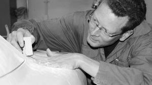 Pasi Pennanen jobbar med händerna på en modell av en bil. Svartvit bild.
