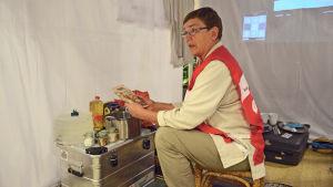 Johanna Westman från Röda korset placerar matvaror i tältets lilla kökshörna.