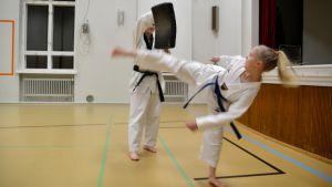 Jessica Stenvall och Emma Johansson tränar taekwondosparkar.
