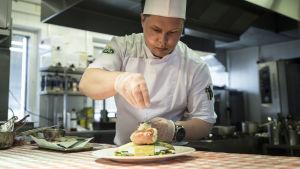 Kocken Viktor Ovtsinnikov strör örter över en vacker matportion.