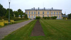 I bakgrunden borgå gymnasiums gula hus, i förgrunden en lång blombänk som är nöstan bara mylla.